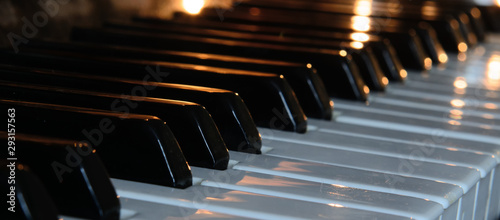 There is a burning candle on the piano keys. Concept - an evening of memories, performance of music. - 293157563