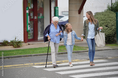 Valokuvatapetti Grandmother, mother and daughter crossing the street