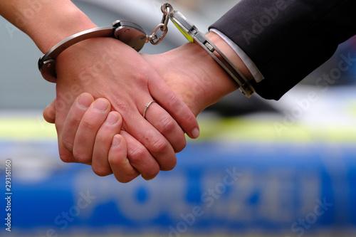 Photo  Die mit Handschellen aneinander gefesselten Hände eines jungen Ehepaares vor ein