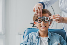 Child Boy In Glasses Checks Eye Vision At Pediatric Ophthalmologist