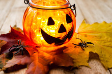 Halloween Concept. Jack-o-lantern Candle Holder With Pumpkins, Spiders, Leaves On Wooden Background