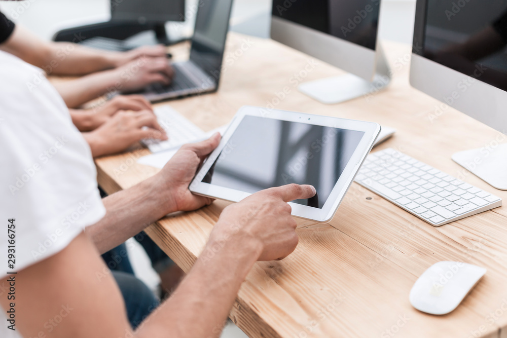 Fototapeta close up. the employee uses a digital tablet in the workplac