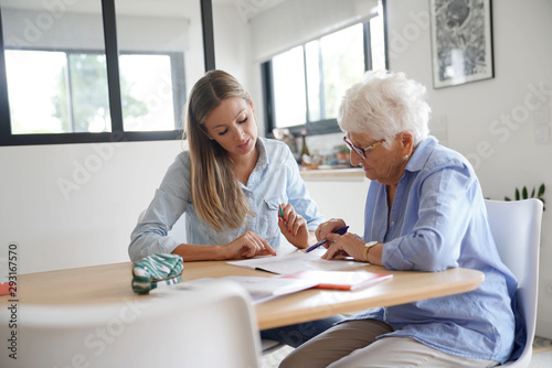 Photo Homehelp assisting elderly woman with paperwork
