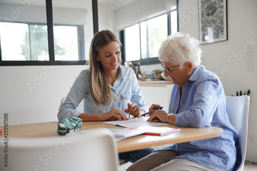 Fotografía  Homehelp assisting elderly woman with paperwork