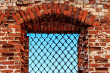 Window With Iron Grating In A Wall Of Ancient Red Brick Building