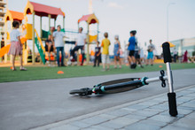Scooter Lies On The Sidewalk In The Background Of A Children's Playground