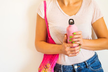 Zero Waste Concept. Young Woman With Pink Reusable Mesh Shopping Bag With Fruit And Stainless Thermo Water Bottle. Plastic Free Lifestyle