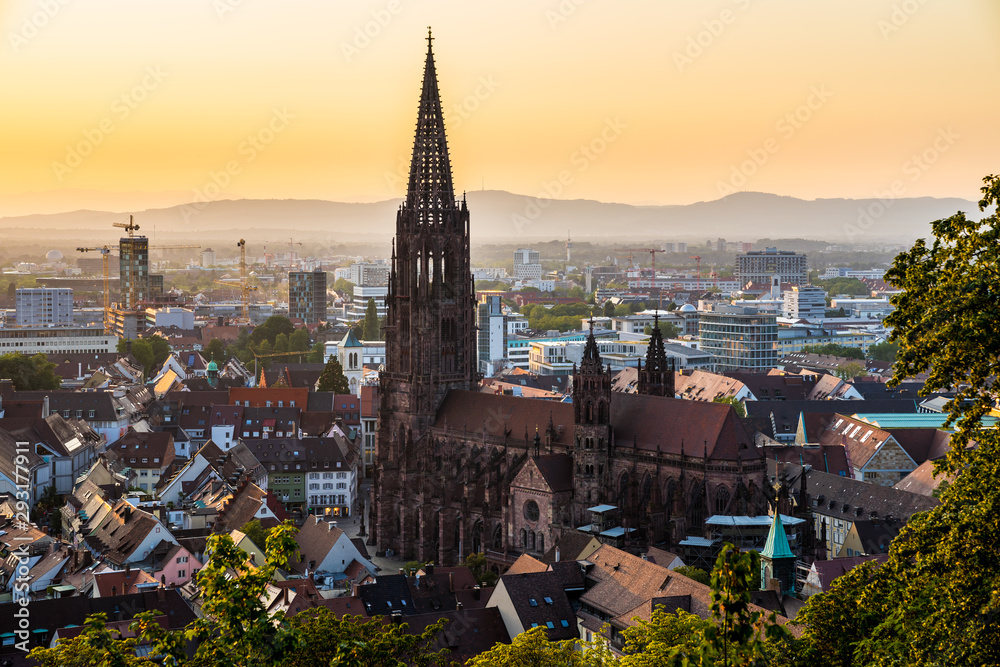 Germany, Black forest city freiburg im breisgau in baden in fantastic sunset twilight atmosphere, aerial view on muenster church from above the houses