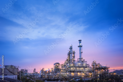 Fototapeta Oil and gas refinery plant or petrochemical industry on blue sky sunset background, Factory at twilight time, Gas furnace and smoke stack in petrochemical industrial obraz