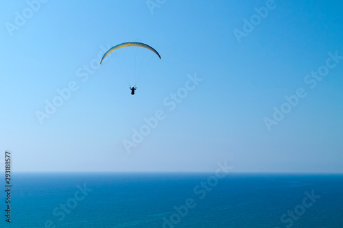 Poster Individuel Paraglider in the sky over blue sea