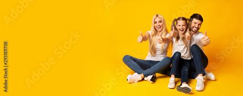 Valokuvatapetti Excited Family Gesturing Thumbs Up Sitting On Floor, Studio Shot