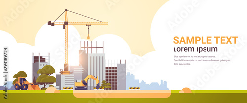Obraz modern construction site with cranes tractor and bulldozer unfinished building exterior sunset background flat horizontal copy space - fototapety do salonu