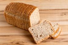 Sliced Loaf Of Whole Wheat Toast Bread Isolated On Light Wood. Three Slices Lying.