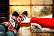 canvas print picture Woman legs with wool socks and window space of winter time