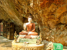 Pai / Thailand - 02.2007. Buddha Statue Standing In A Recess Of A Rock. Nearby Is A Donation Box And Two Wooden Bookcases. Buddha's Face Illuminated By The Bright Sun