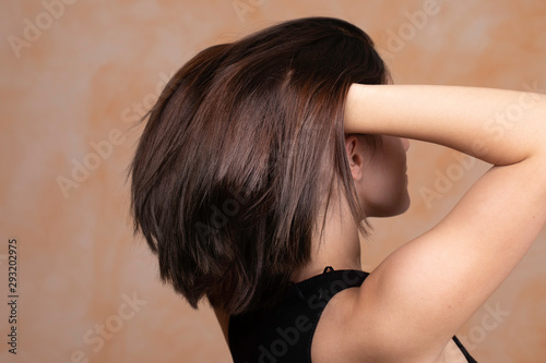 Carta da parati A stunning and sensual young caucasian woman is seen from the rear, using hand to fling hair upwards, soft and conditioned straightened brunette with room for copy