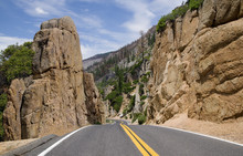 California Scenic Mountain Road:  A Two Lane Highway Passes Through A Cut Between Large Rocks As It Crosses The Sierra Nevada Mountains On The Way To Sonora, CA.