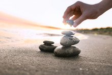 Woman Stacking Dark Stones On Sand Near Sea, Space For Text. Zen Concept