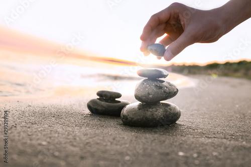 Photo sur Toile Zen pierres a sable Woman stacking dark stones on sand near sea, space for text. Zen concept