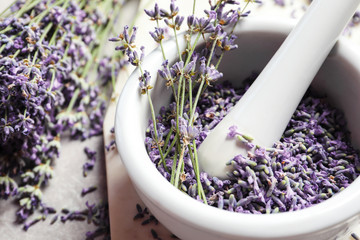 Fototapeta Lawenda Mortar and pestle with lavender flowers on grey stone background, closeup. Natural cosmetic