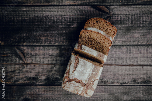 Tuinposter Brood Healthy dark bread and sliced slices on a dark wooden background. The concept of baking bread, eating meals with rolls, bread. Product made of wheat and rye flour, bread preparation.