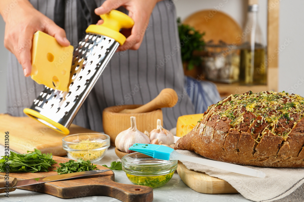 Fototapety, obrazy: Tasty homemade garlic bread with cheese and blurred woman on background