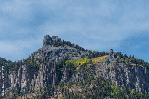 Low angle landscape of grey stone mountain tops with some yellow aspen trees near Ouray, Colorado