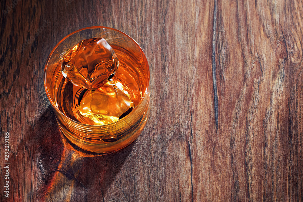 Fototapety, obrazy: Glass of whiskey with ice on wooden bar table