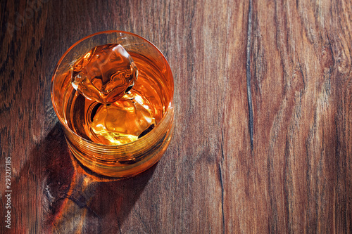 Glass of whiskey with ice on wooden bar table