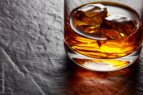 Garden Poster Alcohol Glass of elegant whiskey with ice cubes on black stone table