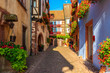 Leinwanddruck Bild - Narrow street and beautiful historic houses in old part of Riquewihr village, wine route in Alsace region, France