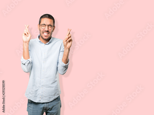 Concerned young man doing a crossed fingers gesture Fototapet
