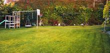 Backyard Garden Of A House With Children Playhouse, Basketball Hoop And Soccer Goal Post