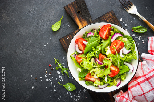 Foto Green salad from leaves and tomatoes.