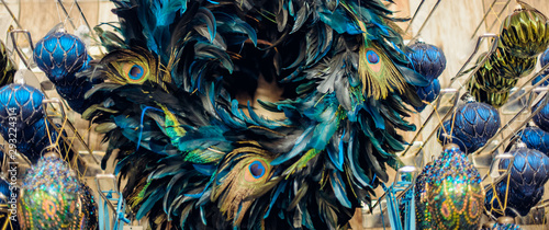 Foto op Aluminium Pauw Close up peacock feather wreath with navy blue and golden balls in shop's display. Close up creative modern Christmas tree decor. Exotic New Year. Trendy colours. Wide banner.
