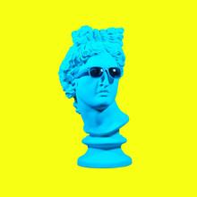 Statue On A Yellow Background. Gypsum Statue Of David's Head. Creative. Plaster Statue Of Apollo's Head In Blue Sunglasses. Minimal Concept Art.