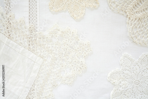 Fényképezés  Layered lace doily and linen background shot from above as graphic resource and