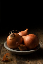 Brown Onions And Shallots In A Stone Bowl, On A Rustic Timber Background.