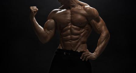 Fitness model man posing in studio