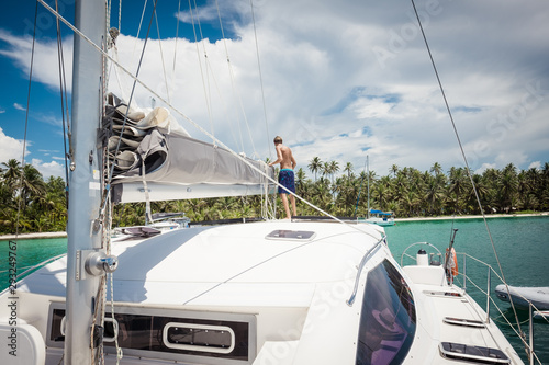 Man preparing mainsail of catamaran Wallpaper Mural