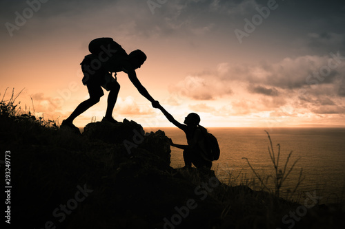 Male mountain climber giving his hand to help his partner Canvas Print