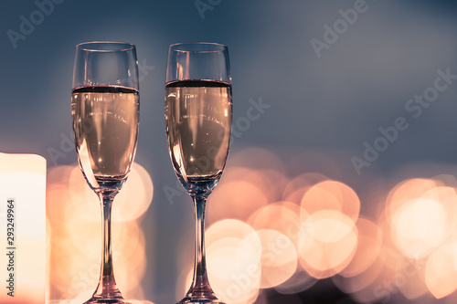 Slika na platnu Pair of champaign glasses against beautiful city light bokeh.