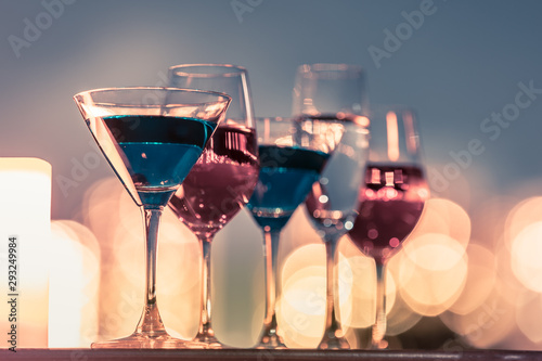 Martini, wine glasses on a bar against beautiful bokeh . City night life concept.