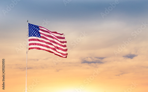 American flag blowing in the wind against beautiful sunset.