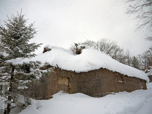 Photo Traditional Japanese Ainu village with straw roof houses with snow drifts in Nob