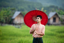 Burmese Men Stand On Grass And Rice Fields, And Asians Use Red Umbrellas To Cover Themselves.