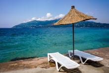 Straw Umbrella And A Pair Of Sunbeds On The Beach Of Saranda, Albania