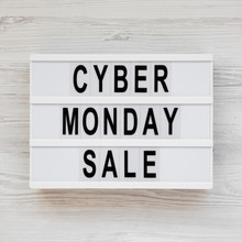 'Cyber Monday Sale' Words On A Lightbox On A White Wooden Surface, Top View. Overhead, From Above, Flat Lay.
