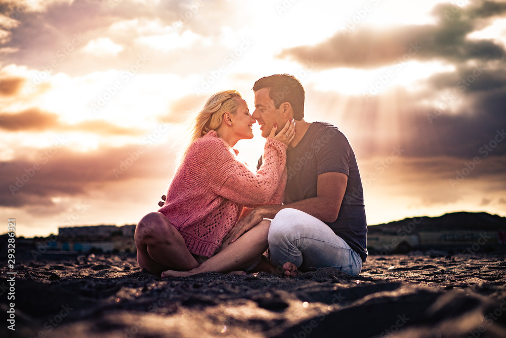 Fototapeta Romantic scenic moment and love concept with couple of young beautiful people hugging and kissing sit down on the ground with golden amazing sunset in backgorund
