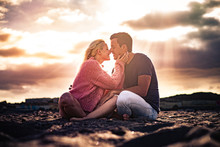 Romantic Scenic Moment And Love Concept With Couple Of Young Beautiful People Hugging And Kissing Sit Down On The Ground With Golden Amazing Sunset In Backgorund